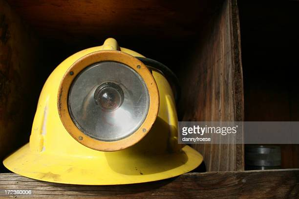Lone mining helmet sitting on a wood shelf