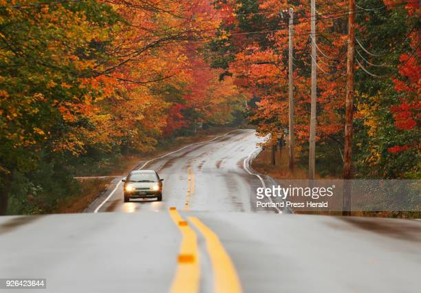 A lone motorist drives amidst a pocket of peak foliage along Rt 35 in Dayton on Monday October 9 2017