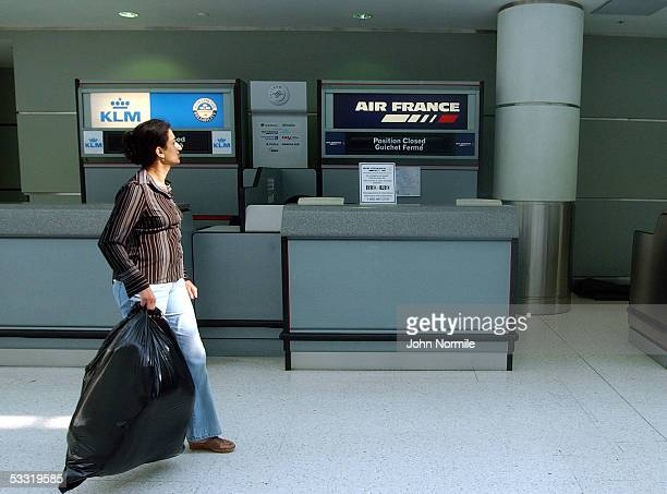 A lone passenger looks for information on outgoing flights at the closed Air France counter at Pearson International Airport a day after the crash of...