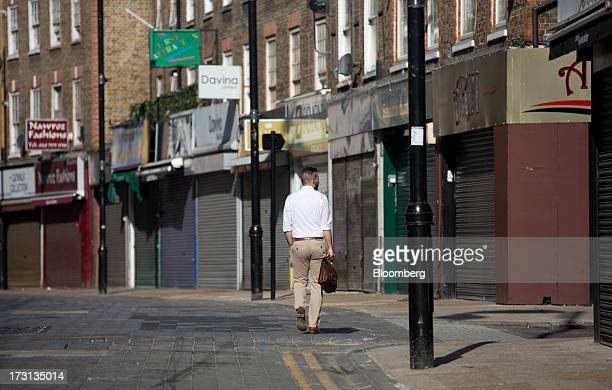A lone pedestrian walks past a row of shuttered and closed stores in London UK on Monday July 8 2013 Britain's economy could be in line for a period...
