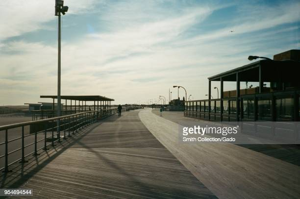 A lone person is visible in the distance walking on the boardwalk at Jones Beach State Park on Long Island Wantagh New York 2018