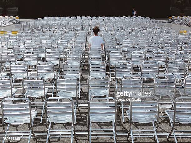 Lone person sitting among many empty chairs