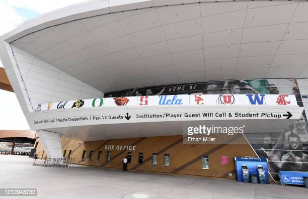 Lone person stands at a row of box office windows underneath the logos of schools that were scheduled to participate in the Pac-12 Conference men's...