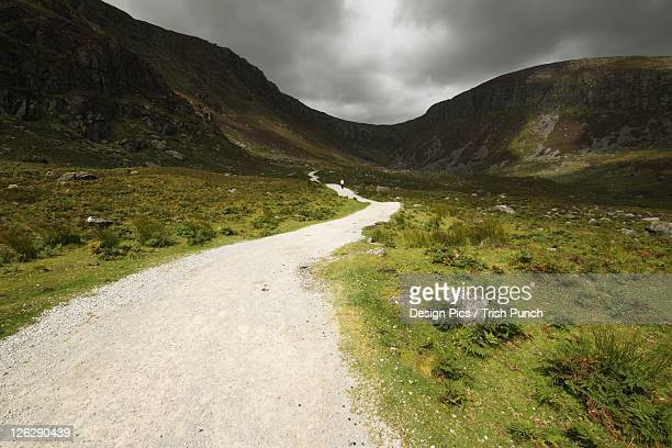 lone person walking on a path leading up to mahon falls in the comeragh mountains in munster region