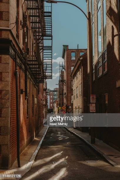 lone person walking through empty alley in littly italy boston - alley stock pictures, royalty-free photos & images