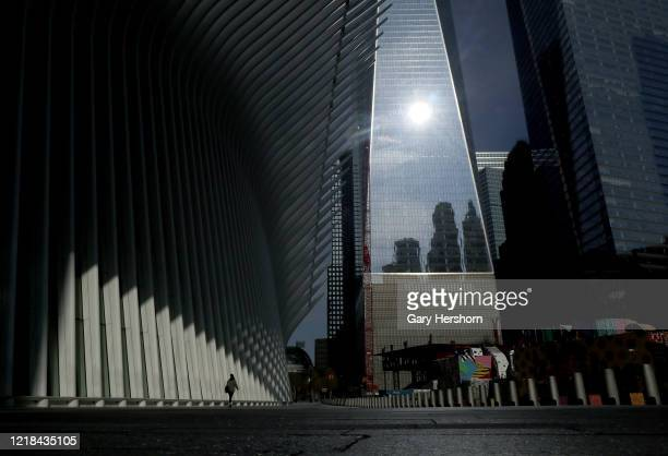 Lone person walks through the empty plaza outside Oculus transit hub and One World Trade Center on Easter Sunday on April 12, 2020 in New York City.