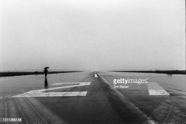 lone person with umbrella in the rain on runway - berlin airlift stock pictures, royalty-free photos & images