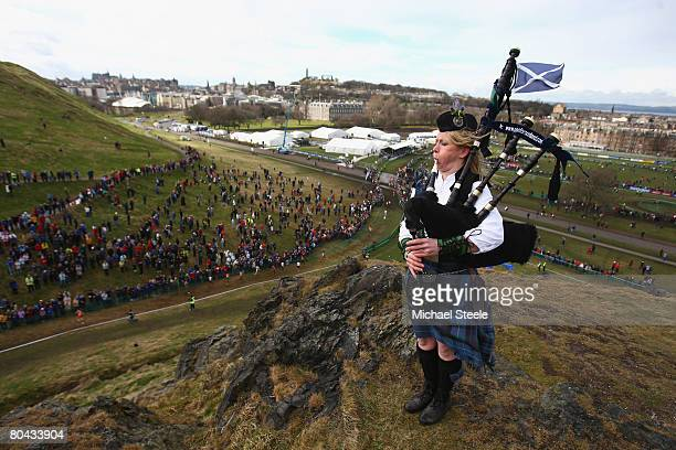 A lone piper plays on top of Haggis Knowe as the men's elite race takes place below during the 36th IAAF World Cross Country Championships at...