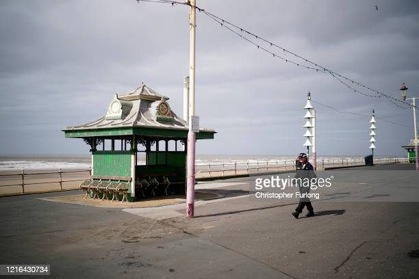 Lone police officer patrols the promenade on Blackpool's Golden Mile as people and businesses observe the pandemic lockdown and stay home on April...