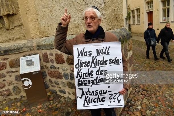 """Lone protester displays a placard reading """"What does this Church want to be: Gospel Church or 'Jew-Pig' Church???"""" as he protests against the..."""