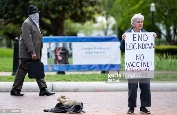 A lone protester holds a sign calling for an end to the lockdown and claiming chloroquine works as she stands in front of the White House in...