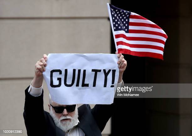 A lone protester holds up a sign and American flag outside the Albert V Bryan United States Courthouse after former Trump campaign chairman Paul...