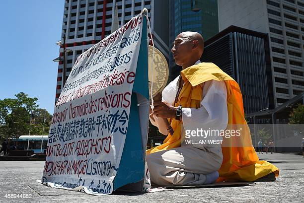 A lone protester sits outside Brisbane's City Hall as Turkey's Prime Minister Ahmet Davutoglu delivers a speech during the G20 Leader's Summit in...