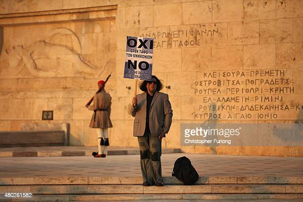 A lone protester stands on the steps in front of the parliament as demonstrators march through Athens during an antiausterity rally ending in front...