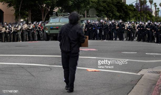 A lone protester tries to confront a line of advancing Riverside County Sheriff deputies and police ready to fire tear gas and pellets on...