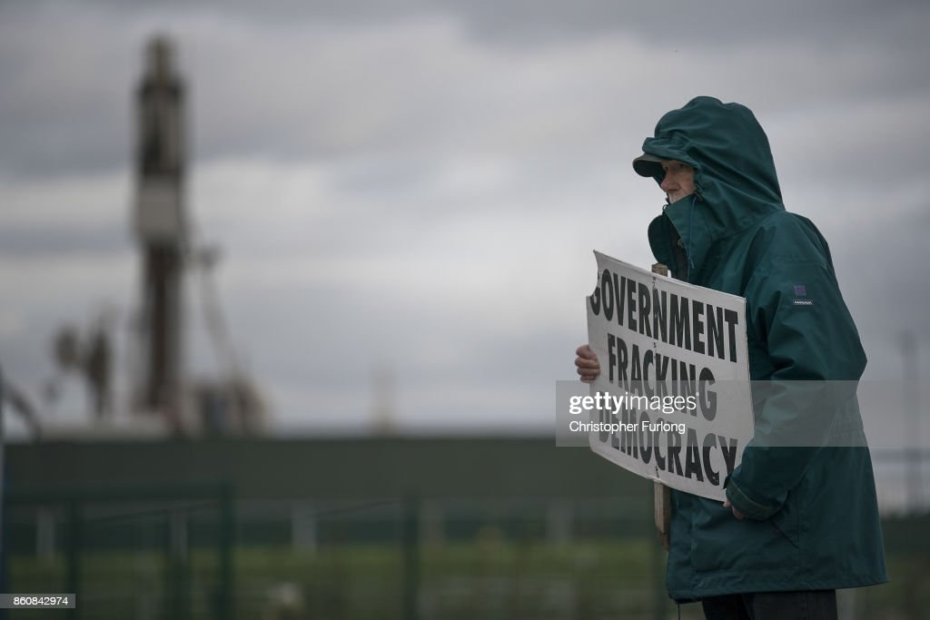 A lone protestor demonstrates outside Workmen Cuadrilla's shale gas fracking drilling rig near Westby on October 12, 2017 in Blackpool, England. Engineers have begun to build the new rig at the site off Preston New Road in preparation for extracting gas. The site will be the first in the UK to extract shale gas since 2011.