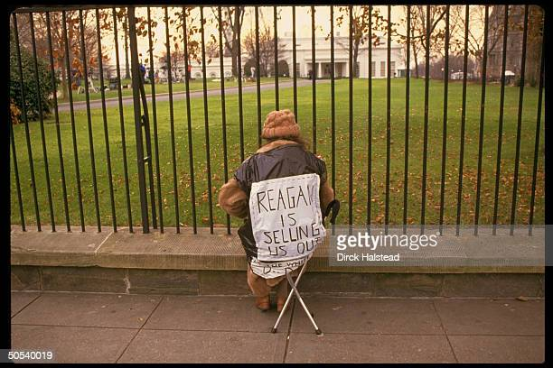 Lone protestor sitting in chair with poster emblazoned with REAGAN IS SELLING US OUT attached to it outside gates of the West Wing of the White House...