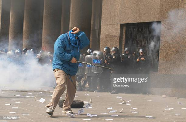 A lone protestor tries to shield himself as police use tear gas to repel demonstrators at the entrance of the Finance Ministry where International...