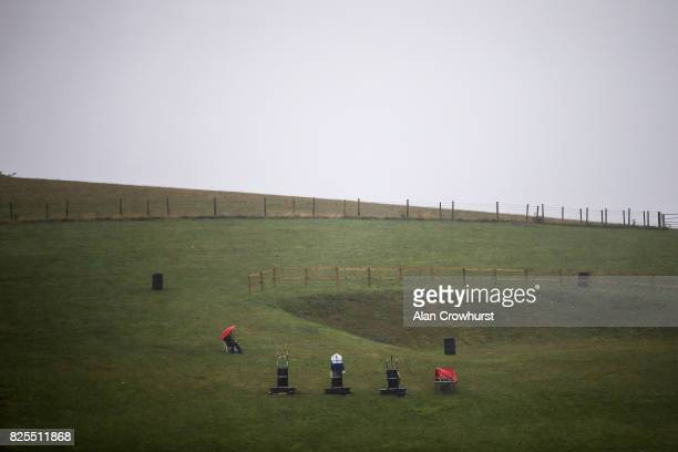 A lone racegoer watches the racing from Trundle Hill with empty bookmaker stands on a wet a misty day on day two of the Qatar Goodwood Festival at...