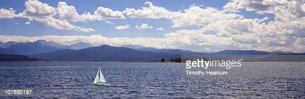 lone sailboat on sparkling mountain lake - timothy hearsum stock-fotos und bilder