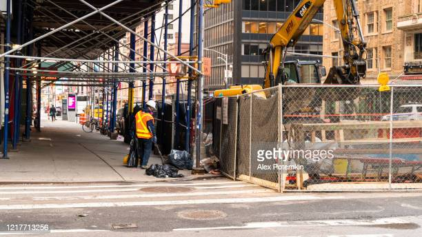 a lone sanitation worker is cleaning a street in midtown manhattan that is deserted during a coronavirus pandemic. - alex potemkin coronavirus stock pictures, royalty-free photos & images