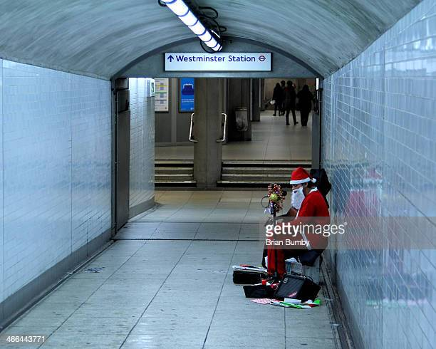 CONTENT] Lone Santa playing guitar in Westminster Station Westminster London UK
