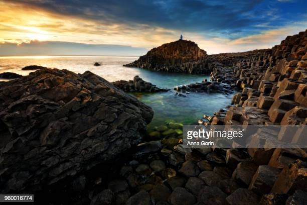 Lone silhouetted tourist on top of basalt columns forming famous Giant's Causeway in Northern Ireland, long exposure at sunset