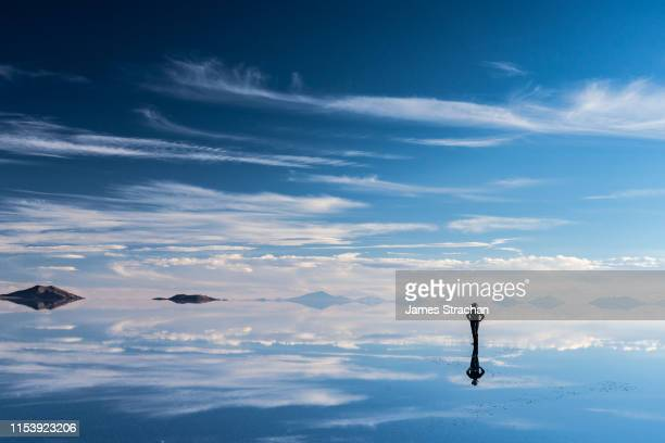 lone, silhouetted traveler in safari hat stops to admire the beauty of the salt flats which are reflecting the clouds and mountains after rainfall, uyuni, bolivia - ボリビア ストックフォトと画像