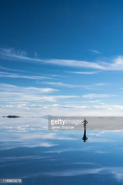 lone, silhouetted traveler in safari hat stops to admire the beauty of the salt flats which are reflecting the clouds and mountains after rainfall, uyuni, bolivia - 空気感 ストックフォトと画像