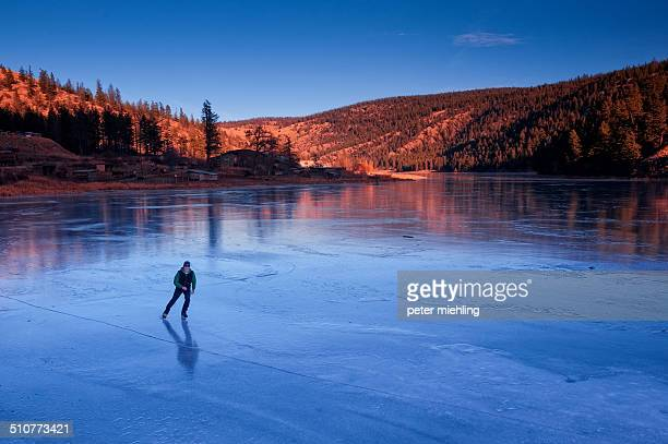 Lone skater practices his skills on the a frozen Shumway Lake during the late afternoon sun on a crisp December day near Kamloops, BC, Canada.