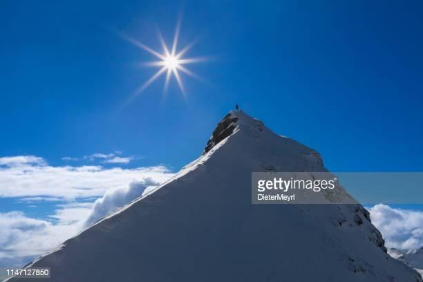 lone ski climber on the summit  - mount pilan - lofoten - mountain peak stock pictures, royalty-free photos & images