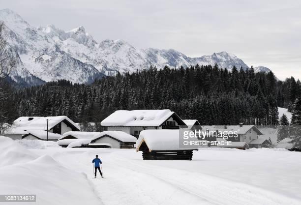 A lone skier glides trough the snowcovered landscape near the small Bavarian village of Kruen near GarmischPartenkirchen southern Germany on January...