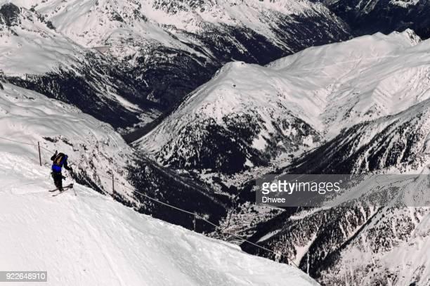 lone skier on mountain ridge against snowcapped mountains - valle blanche fotografías e imágenes de stock
