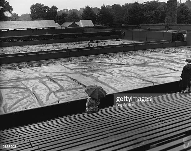 Lone spectator waiting for the rain to stop in front of the covered courts at the Wimbledon Lawn Tennis Championships.