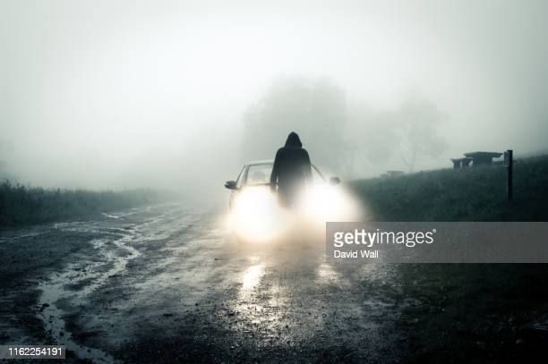 a lone, spooky, hooded figure standing in front of a car looking at an empty misty country road silhouetted at night by car headlights. - hooded top stock pictures, royalty-free photos & images