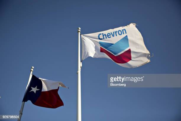 Lone Star and Chevron Corp flags fly outside an office building in Midland Texas US on Thursday March 1 2018 Chevron the world's thirdlargest...