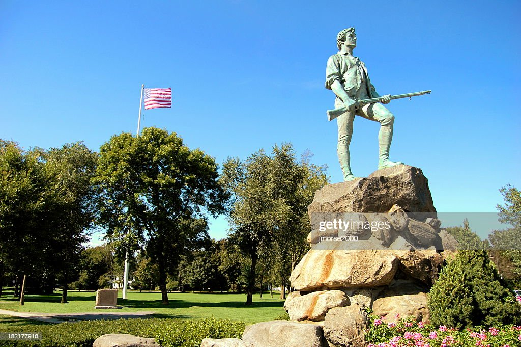 Lone statue on top of rock with American flag flying behind : Stock Photo