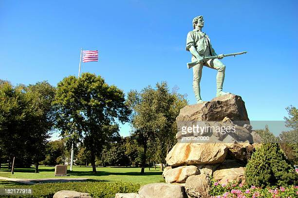Lone statue on top of rock with American flag flying behind