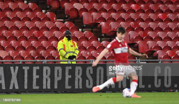 Lone steward, wearing a face covering watches the action in front of an empty stand during the Sky Bet Championship match between Middlesbrough and...