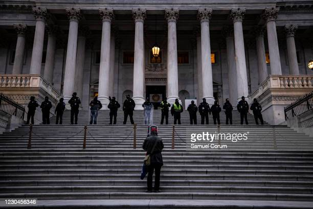 Lone supporter of President Trump stands on the steps to the U.S. Capitol below a line of police in riot gear after a pro-Trump mob stormed the U.S....