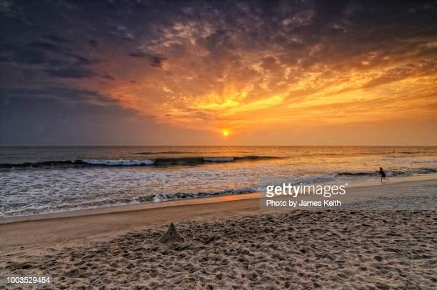 a lone surf fisherman casts into the sea amid a colorful sunrise on playalinda beach, canaveral national seashore. - titusville florida stock pictures, royalty-free photos & images