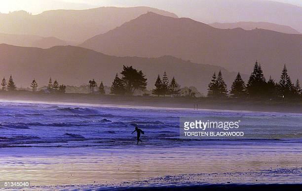 A lone surfer braves the icy waters of Poverty Bay at Gisborne's Waikanae Beach 30 November 1999 where local girl and soprano diva Dame Kiri Te...