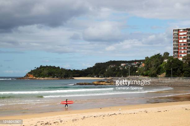 A lone surfer walks up the beach at Manly Beach on March 23 2020 in Sydney Australia The state of New South Wales in Australia has the highest number...