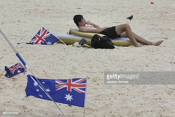 A lone swimmer lies on the beach braving the unusually cold and windy weather at Bondi beach on Australia Day on January 26 2015 in Sydney Australia...
