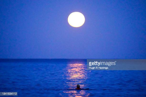 Lone swimmer takes to the sea to swim under the Harvest Moon on September 20, 2021 in Swanpool Beach, Falmouth, England.