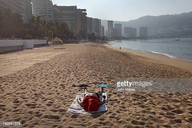 A lone tourist lies out on the beach early on March 2 2012 in Acapulco Mexico Drug violence surged in the coastal resort last year making Acapulco...