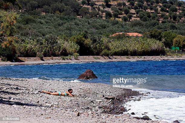 A lone tourist sunbathes on an empty beach which was one of the main landing points for refugees on 19 July in Skala Kaminas Lesvos Island GreeceThe...