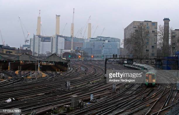 Lone train is pictured as it approaches Victoria Station with Battersea Power Station in the background on March 19, 2020 in London, England .