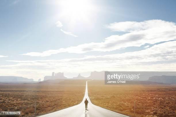 lone traveller walking down empty road towards distant cliffs - 道 ストックフォトと画像