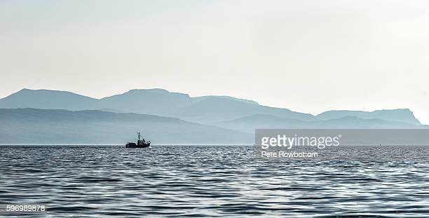lone trawler passes the isle of rum - paysage marin photos et images de collection